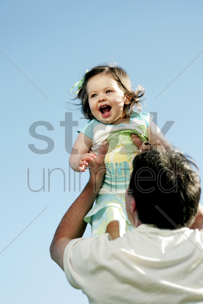 man lifting up his daughter stock photo