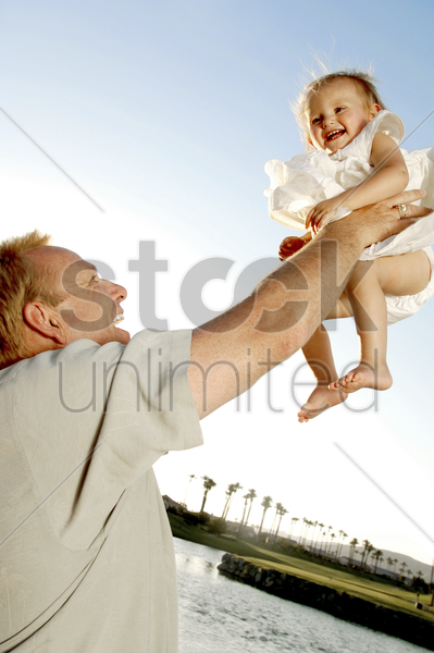 man lifting up his young daughter stock photo