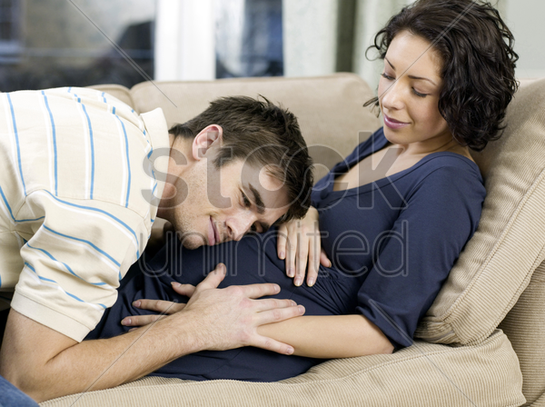 man listening to his pregnant wife' stomach stock photo