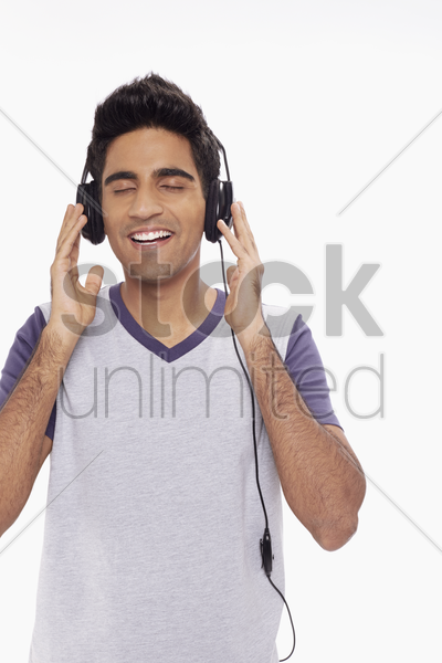 man listening to music on headphone stock photo