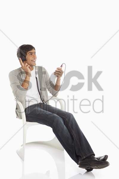 man listening to music on mobile phone stock photo