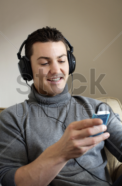 man listening to music on portable mp3 player stock photo