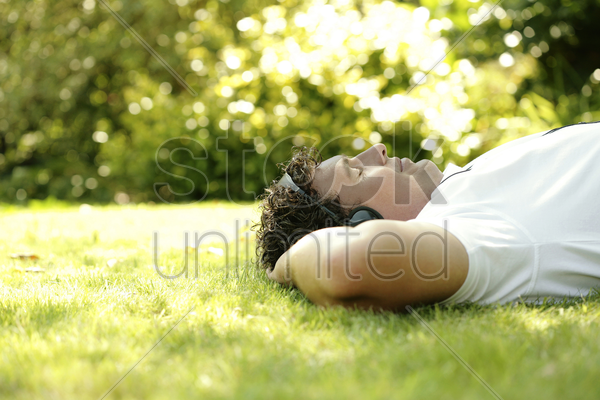man listening to music on the headphones while lying on the field stock photo