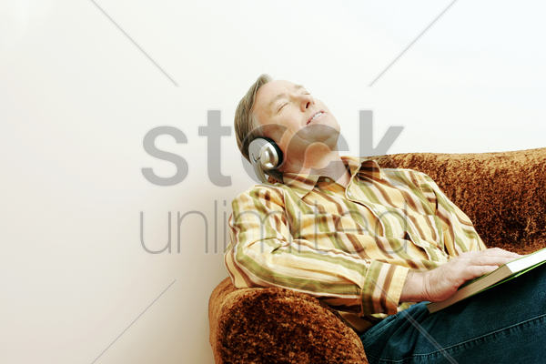 man listening to music while reading book stock photo