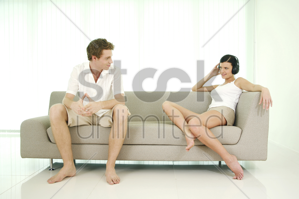 man looking at his girlfriend listening to music on the headphones stock photo