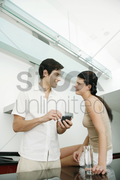 man looking at his girlfriend while using palmtop stock photo