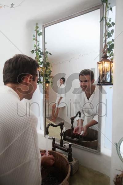 man looking at mirror reflection of woman while washing his hands stock photo