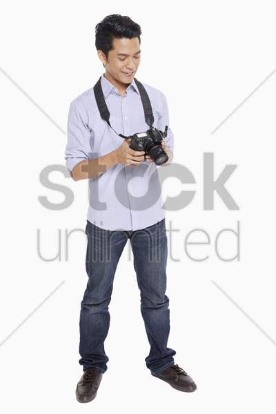 man looking at pictures from his digital camera stock photo
