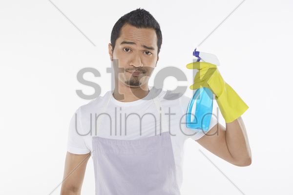 man looking at the camera while holding a spray bottle stock photo