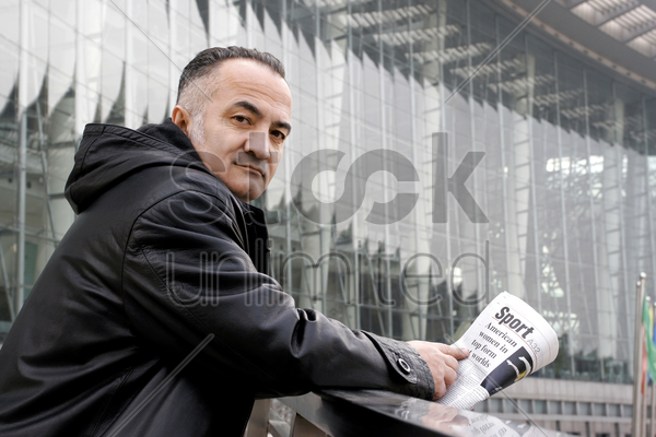 man looking at the camera while holding newspaper stock photo