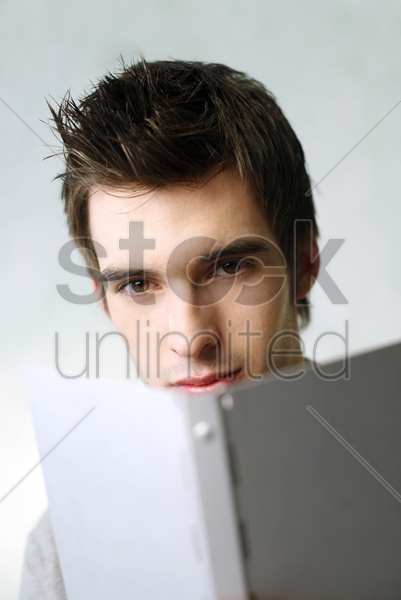 man looking at the camera while reading book stock photo
