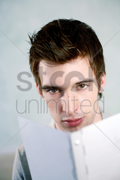 man looking at the camera while reading stock photo