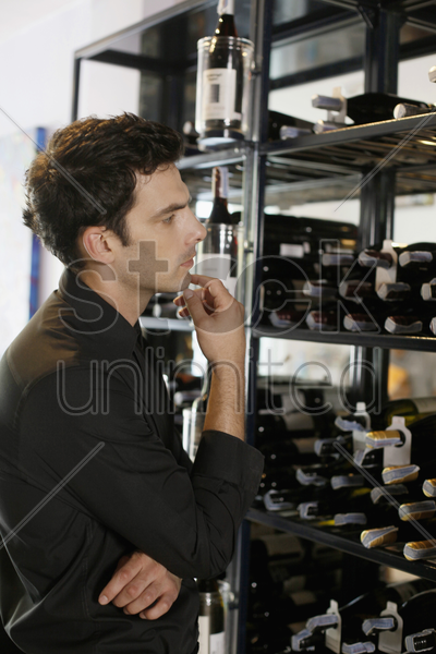 man looking at wines in a restaurant stock photo