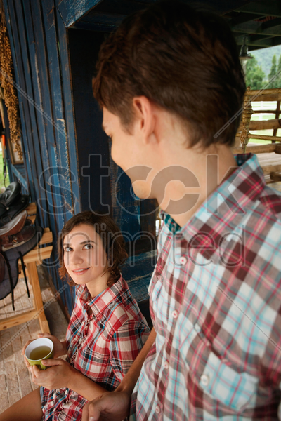 man looking at woman holding a cup of tea stock photo