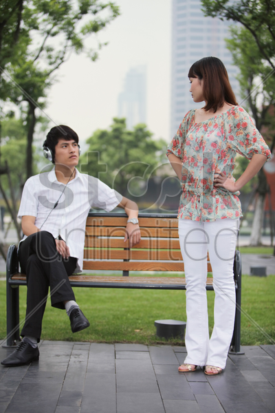 man looking at woman while listening to music on the headphones, woman scolding man with her arms akimbo stock photo