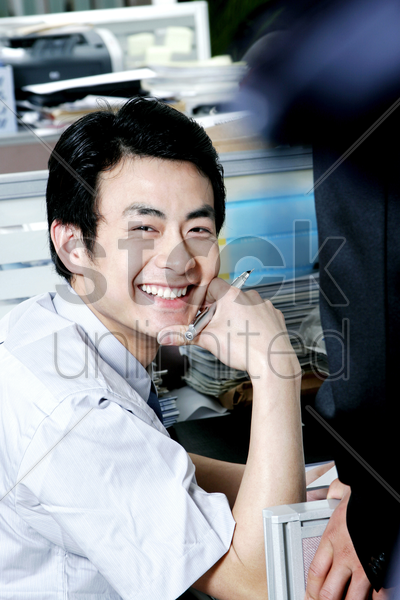 man looking happy sitting at his desk stock photo