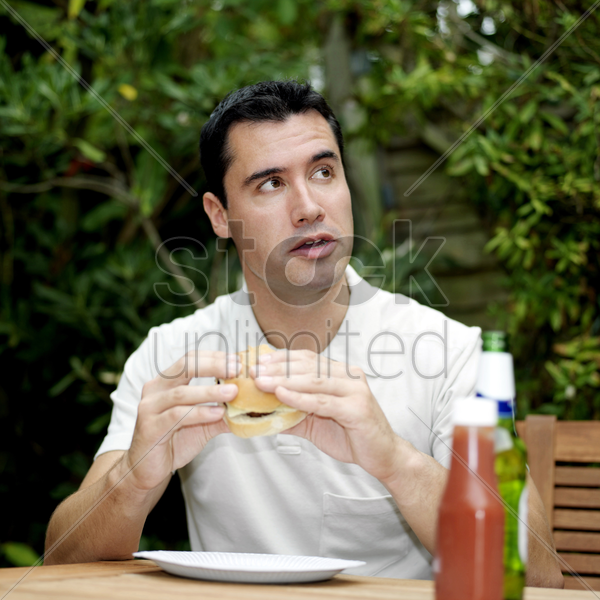 man looking up while holding a burger stock photo