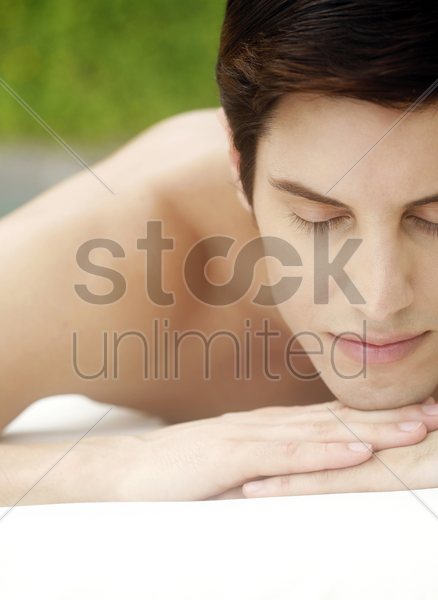 man lying forward on a massage table with his eyes closed stock photo