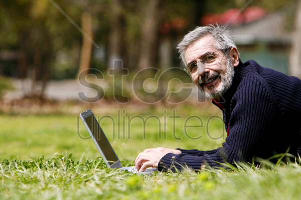 man lying forward on the grass using laptop stock photo