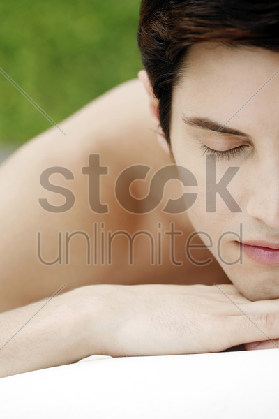 man lying forward with his eyes closed stock photo