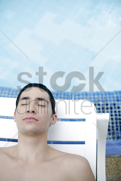 man lying on lounge chair with his eyes closed stock photo