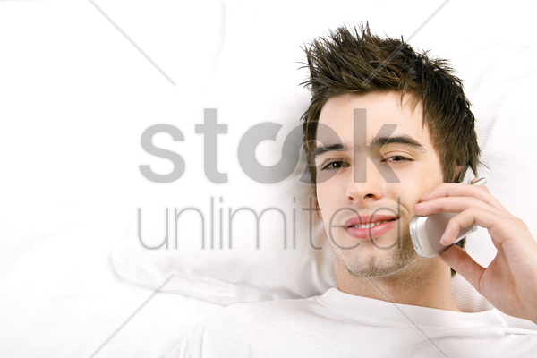 man lying on the bed talking on the mobile phone stock photo