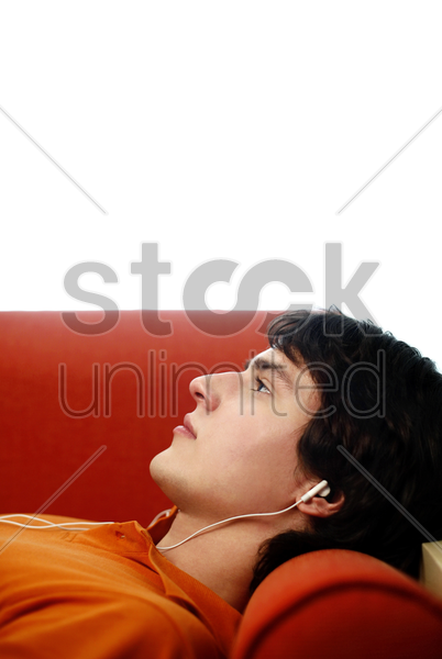 man lying on the couch listening to music on the earphones stock photo