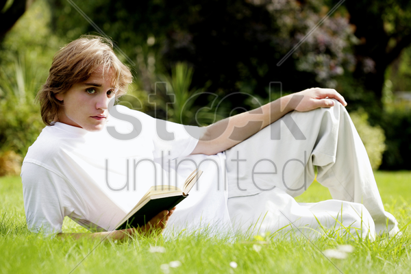 man lying on the grass holding a book stock photo