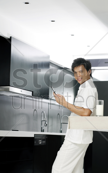 man making a phone call in the kitchen stock photo