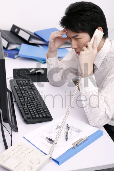 man massaging his head while talking on the phone stock photo
