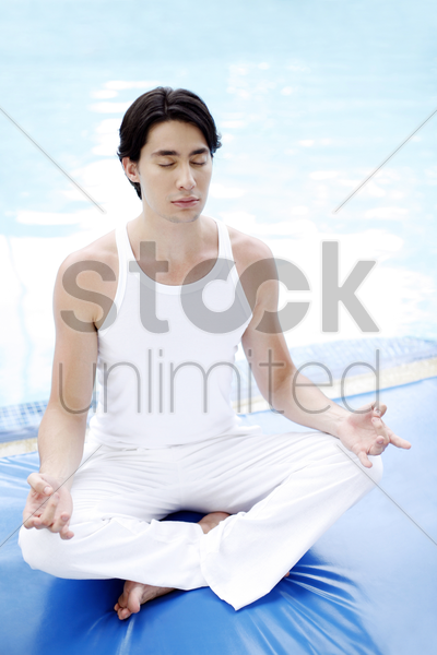 man meditating by the pool side stock photo