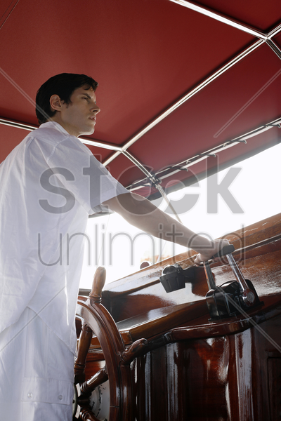 man navigating a yacht stock photo