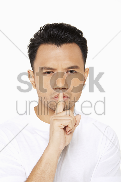 man placing finger on his lips stock photo