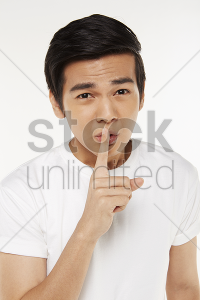 man placing finger on lips stock photo