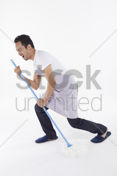 man playing around while cleaning stock photo