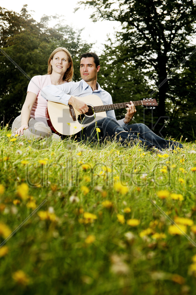 man playing guitar for his girlfriend while sitting in the park stock photo
