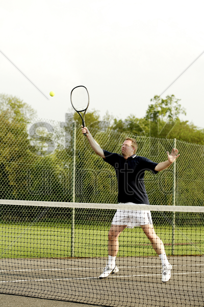 man playing tennis in the tennis court stock photo