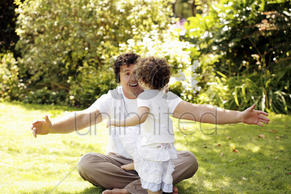 man playing with his daughter while listening to music on the headphones stock photo