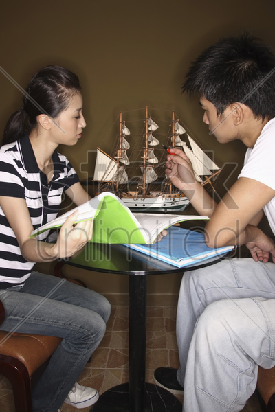 man pointing at ship model, woman with book watching stock photo