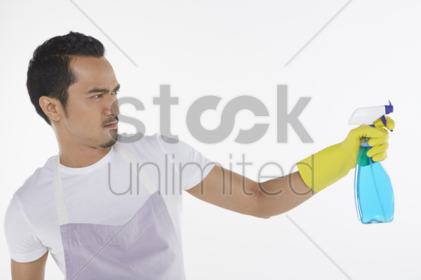man pointing spray bottle to the left stock photo