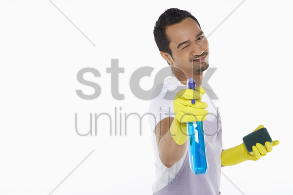 man pointing spray bottle towards the camera stock photo
