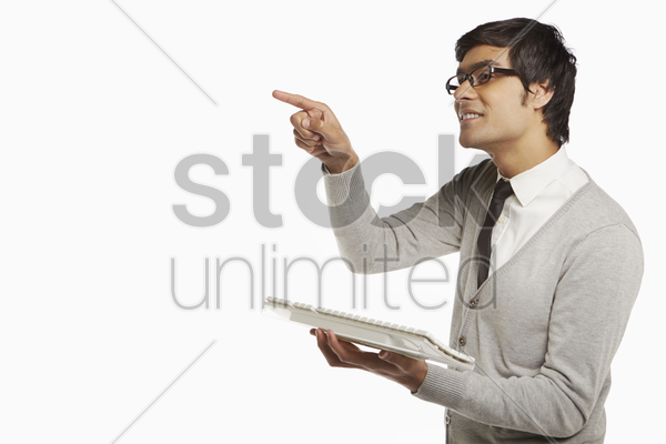 man pointing to the right while using computer keyboard stock photo