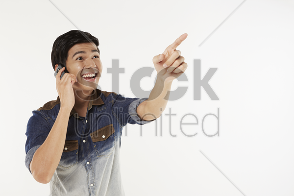 man pointing while talking on the phone stock photo