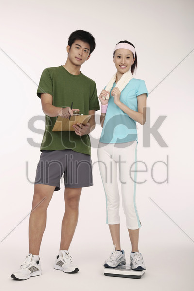 man posing beside woman on weight scale stock photo