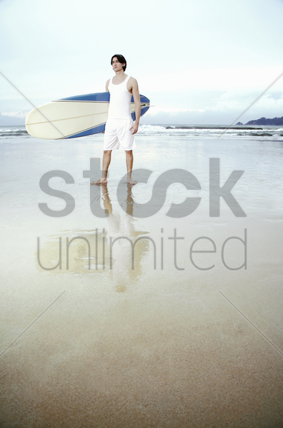 man posing with a surfboard stock photo