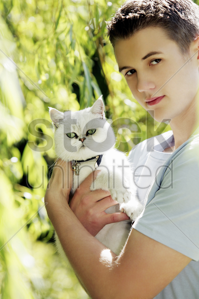 man posing with a white cat stock photo