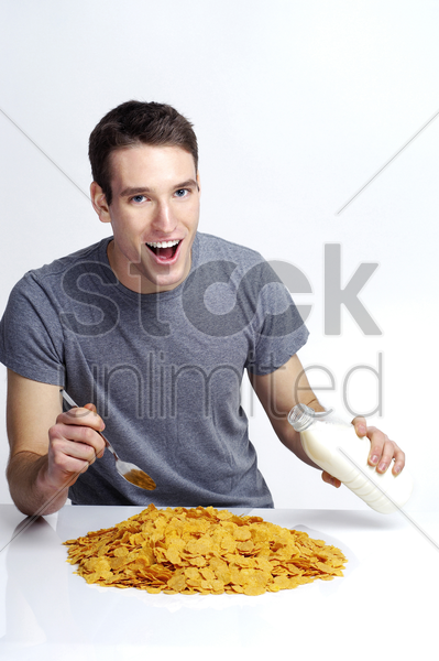 man pouring a bottle of milk onto a pile of cereal stock photo