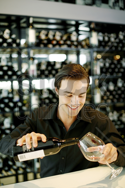 man pouring a bottle of wine into the glass stock photo