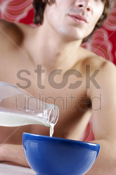 man pouring milk into his breakfast cereal stock photo