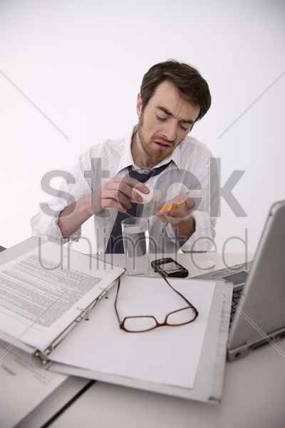 man pouring pills from plastic bottle stock photo